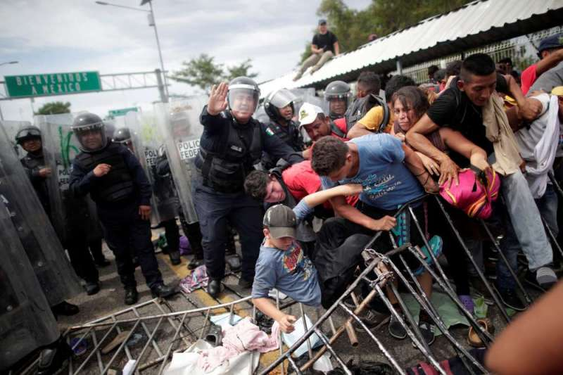 A federal policeman gestures as Honduran migrants, part of a caravan trying to reach the U.S., are being pushed by other migrants after storming the Guatemalan checkpoint to enter Mexico, in Ciudad Hidalgo