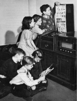 Children watching the comics section of a faxpaper being printed (Gizmodo)