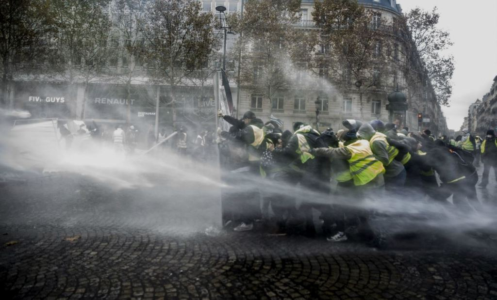 The photograph displays a confrontation that happened during the French 2020 demonstrations. We can easily recognise on the right-side marchers wearing the famous French yellow jacket. They are facing fire hoses on the left side and have turned safety barriers into makeshift shields. The power of the conflict is noticeable through the marchers' gathering behind barriers trying to hold their position despite the water pression.